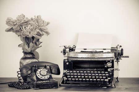 Vintage schrijfmachine, oude telefoon, bloemen op tafel sepia foto