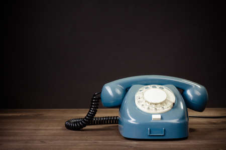 Retro rotary telephone on table against black background