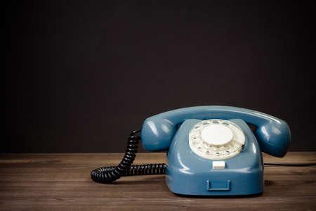 Retro roterende telefoon op tafel tegen een zwarte achtergrond Stockfoto