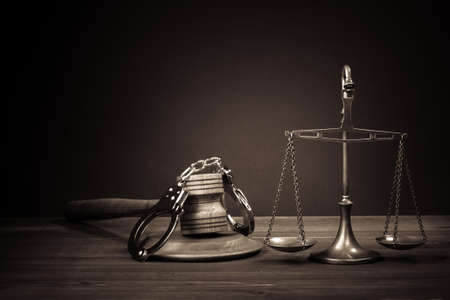 Law scales, judge gavel, handcuff on table  Symbol of justice  Vintage sepia photo Imagens