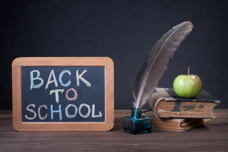 teaching material: Back to School written on a blackboard with pen, books and apple in front of black background