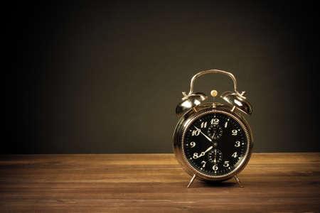 Retro alarm clock on table on dark background photo