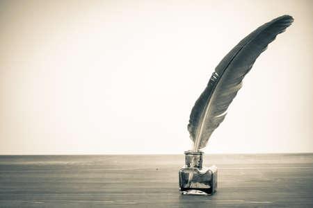 羽根ペンとインク壺のテーブルの上のビンテージ背景