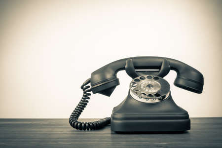 telefono antico: Rotante telefono retrò su tavola con il posto vuoto per sfondo d'epoca Archivio Fotografico