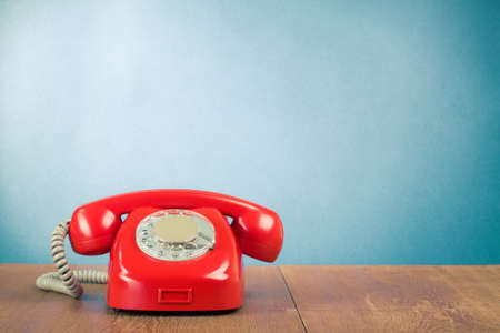 contact icons: Retro red telephone on wood table near aquamarine wall background