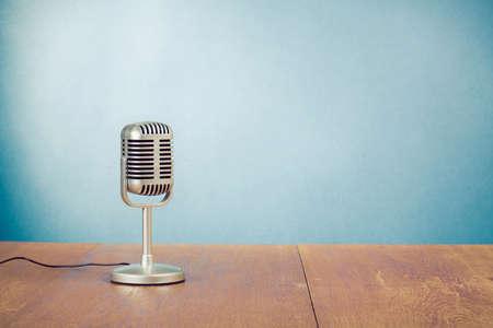 microfono de radio: Micrófono de estilo retro en la mesa cerca de la pared de fondo azul Foto de archivo