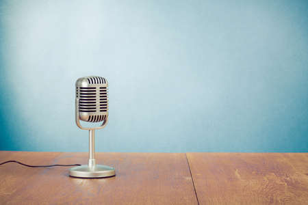 Retro style microphone on table near blue wall background Imagens