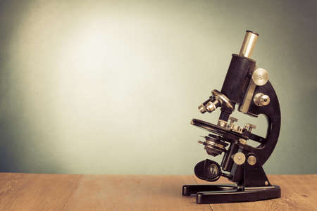 Vintage microscope on table for science background photo