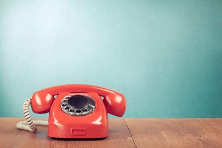 Retro rode telefoon op houten tafel in de buurt van aquamarijn muur achtergrond