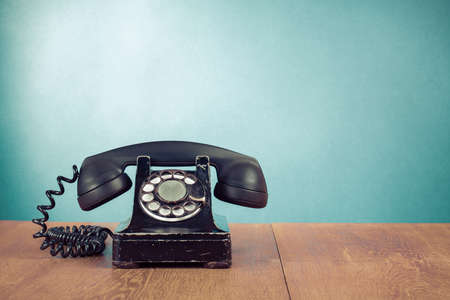 Retro teléfono en la mesa en frente de menta fondo verde Foto de archivo - 23020513