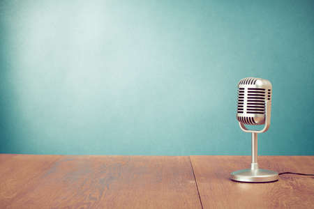 radio microphone: Retro microphone on table in front aquamarine wall background