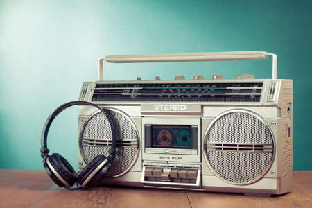 blaster: Retro cassette ghetto blaster and phones on table in front mint green background