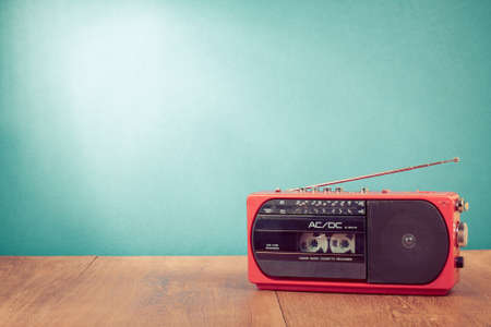 cassettes: Retro red radio cassette player on table in front mint green background