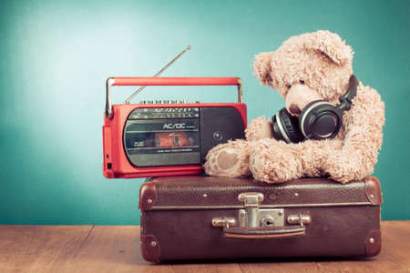 Retro toy bear, old suit case and radio recorder in front mint green background Archivio Fotografico