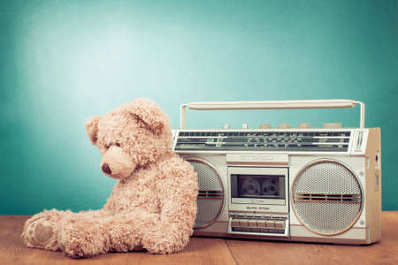 Retro toy bear and radio recorder in front mint green background