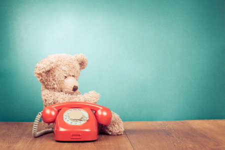 Retro red telephone and teddy bear toy near aquamarine wall background