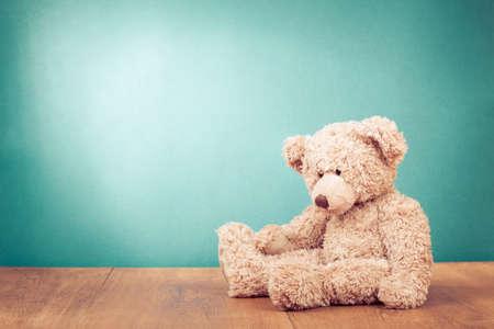 oso de peluche: Juguete del oso de peluche en la madera en perfecto delante de fondo verde