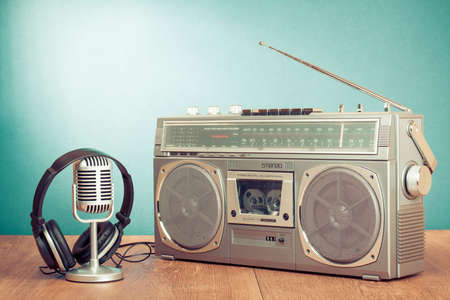 Retro radio and cassette player, headphones, microphone on table in front mint green background
