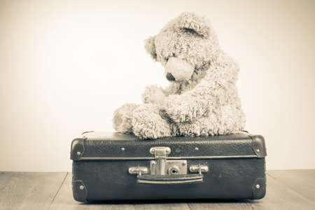 Teddy Bear toy alone on suit case retro sepia photo photo
