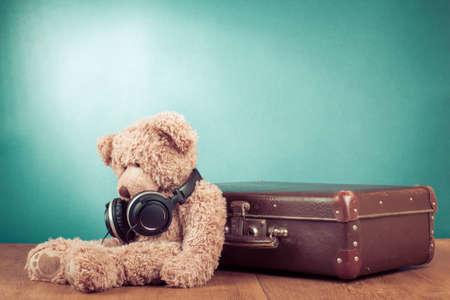 oso de peluche: Retro oso de peluche con auriculares sentado cerca de un antiguo concepto maleta