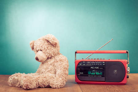 Retro toy Teddy Bear and radio recorder in front mint green background