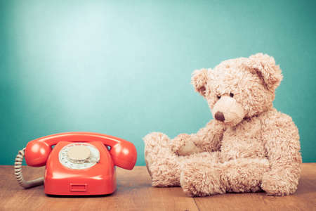 Retro red telephone and Teddy Bear near mint green wall background Standard-Bild