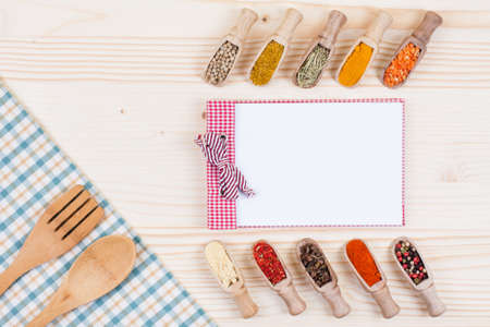 Recipe notebook, spices, checkered tablecloth on wood background