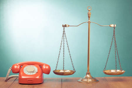 Law scales and retro telephone on table photo