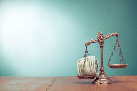 balanza en equilibrio: Escalas de Derecho y el dinero en efectivo en la mesa de la foto del concepto Foto de archivo