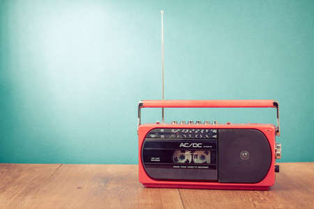 Old retro red radio cassette recorder on table in front mint green background