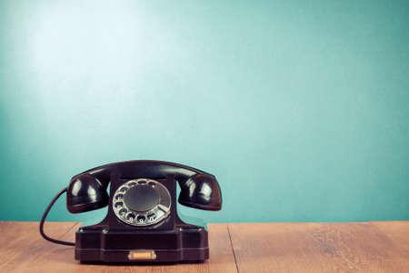 前のテーブルにレトロ黒電話ミントの緑の背景