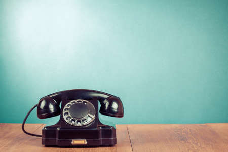 contact us icon: Retro black telephone on table in front mint green background Stock Photo