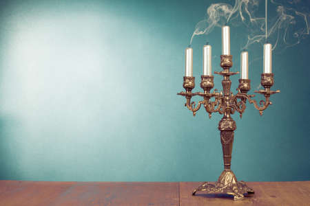 Vintage bronze candlestick with five reek candles in front mint green background