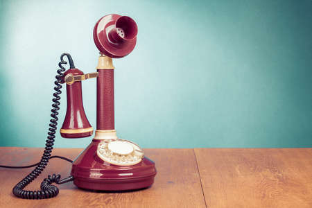 Vintage old telephone on wood table near aquamarine wall background photo