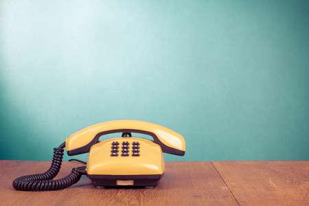 Retro telefono giallo sul tavolo di legno