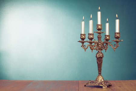 Vintage bronze candlestick with five burning candles in front mint green background