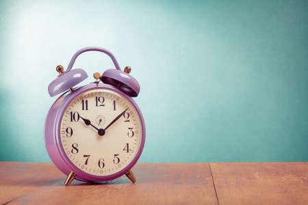 despertador: Reloj de alarma retro en la mesa delante de fondo verde menta