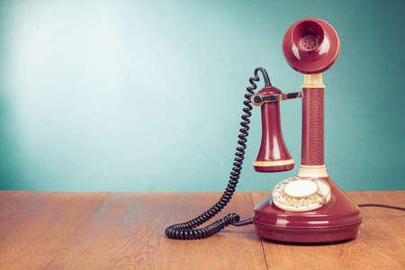 Oude retro telefoon op houten tafel voor mint groene achtergrond