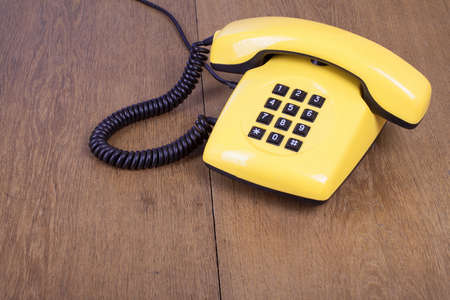 Retro yellow telephone on old wooden table background