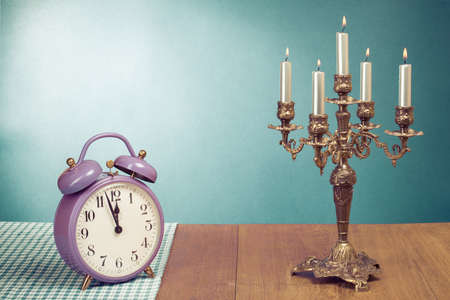 Retro clock and candle holder on table front mint green background photo