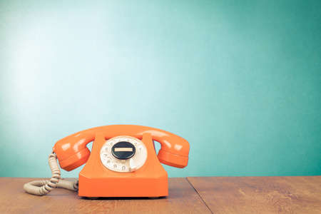Retro orange telephone on wood table near aquamarine wall background photo