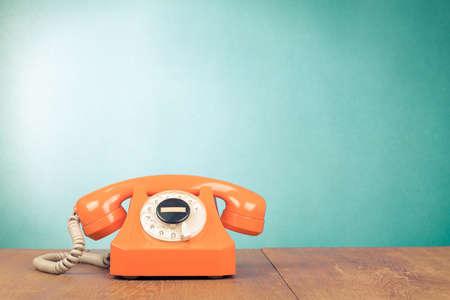 telephone: Retro orange telephone on wood table near aquamarine wall background Stock Photo