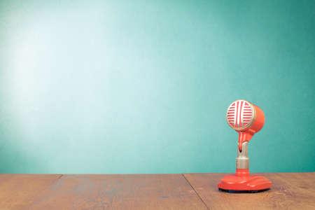 Retro microfono rosso sul tavolo davanti a sfondo verde menta