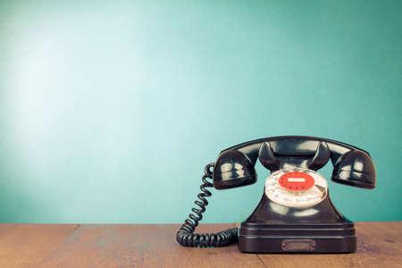 Retro black telephone on table front aquamarine background