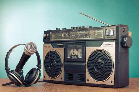 Old retro radio cassette player, headphones, microphone on table