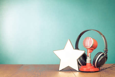 Retro microphone, headphones and winner star in front aquamarine wall background