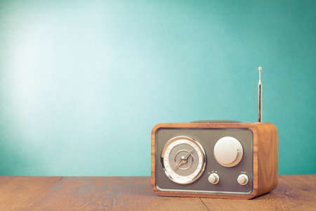 Retro style radio receiver on table in front mint green background 版權商用圖片