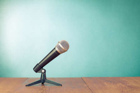 Classic microphone on table front aquamarine wall background