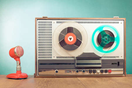 Retro reel tape recorder and microphone in front mint green background