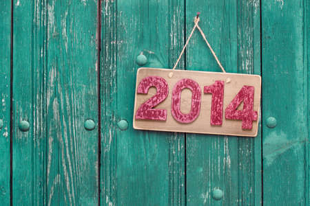 Vintage New Year date sign board on wooden planks background hanging on nail photo